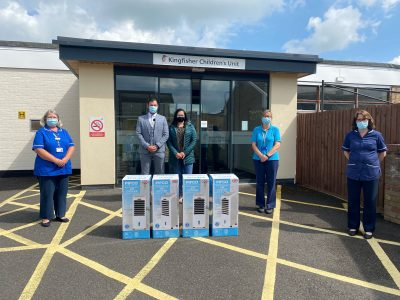 Three nurses and a man and a woman in front of four air conditioning boxes
