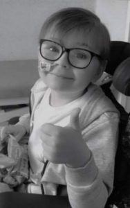 A boy with glasses doing a thumbs up gesture with his left hand